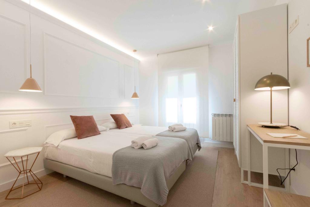 Habitación con cama, mesilla y mesa auxiliar